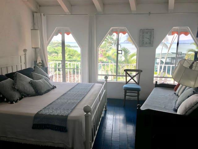 Cuarto principal con cama king y un sofá cama baño y balcón