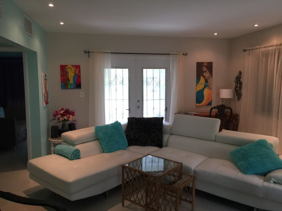 Spacious living room with new leather sectional, TV, wireless Internet, and terrazzo floors. Original art throughout home. French doors lead to private screened in porch.