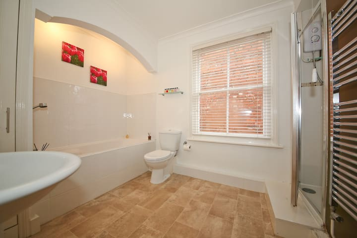 Large family bath/shower room with heated towel rail and complimentary towels.