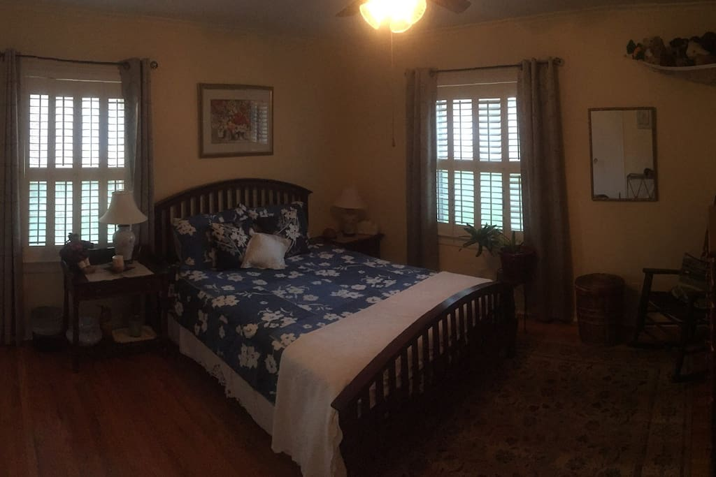 Comfortable private queen bed with view of dogwood trees and garden. Room has blackout curtains and rocking chair.