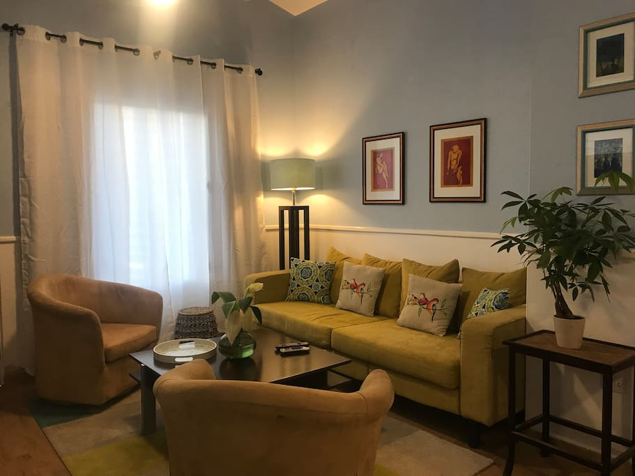 """The living room is part of an open concept, which includes the dining area and the """"business center.""""    The apartment has cathedral ceilings, 12 feet tall. It's cooled with air conditioner and fans."""