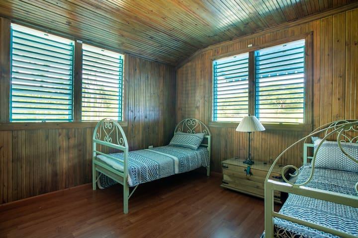 Habitación con dos camas individuales junto un hermoso panorama en madera