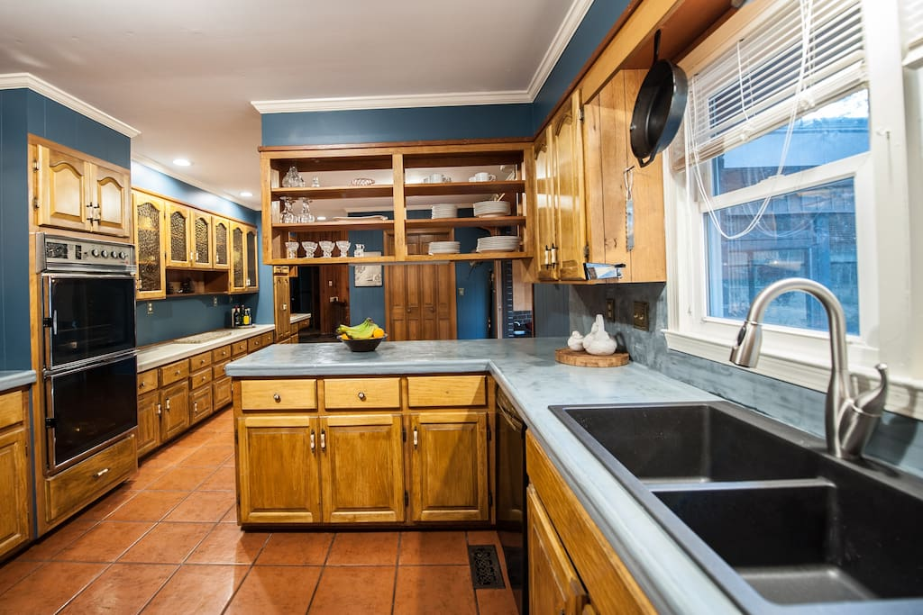 large kitchen featuring electric stove, large refrigerator, dishwasher, and double oven.