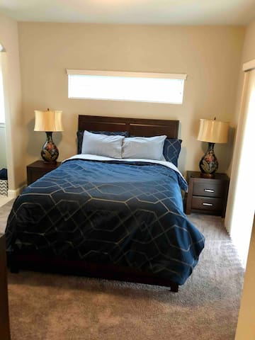 """Master bedroom. Queen sized bed with 55"""" mounted television with Dish Network. Walk-in closet. Private bathroom and shower. Outside access to backyard patio."""