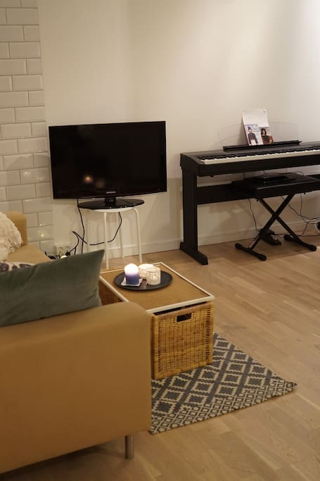 The apartment has both TV, piano and guitar