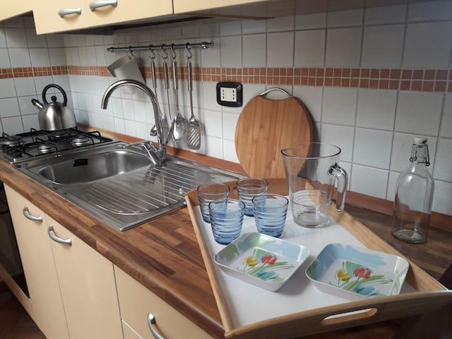 Cucina completamente attrezzata, piano cottura, forno, frigo, congelatore, piastra elettrica, tostapane, frullatore ad immersione, stoviglie, posate, mestolame, utensili, tovaglie, strofinacci.