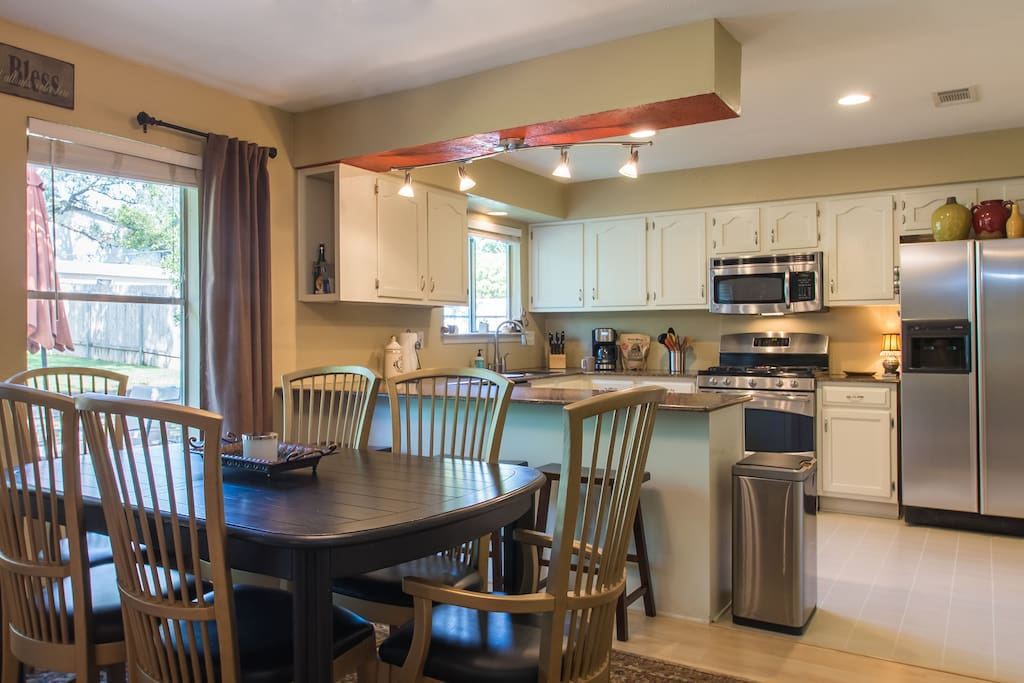 Open concept kitchen and dining with seating for 9 people between the table and bar top.  Extra table leaflets also available to extend table 3 feet if needed.  Kitchen is fully stocked to cook and serve even a nice holiday meal.