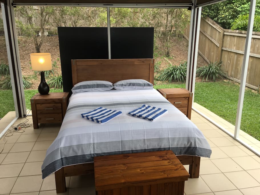 Sleep indoor but outdoors in this queen size bed that is in an out doors full fly screened and with full block out privacy blinds. A large fan above the bed and electricity with access to the house shower and toilet. It's the ultimate indoor outdoor experience . A colour bond water right above you so if it rains the sound is amazing.