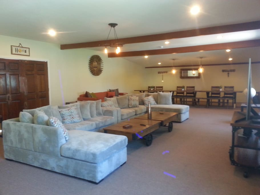 This is our extra large family room for groups to gather. This room is off our backyard garden area, off the main house. Great for meetings and gatherings, and watching movies. We have Netflix.  The dining tables seat 16 people.