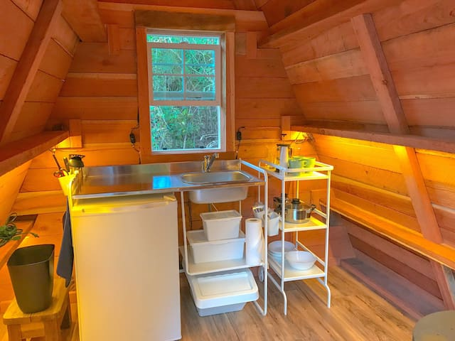 Kitchen inside has a mini fridge & freezer, and sink (water is not heated). There is a coffee press, pots and pans, bowls, plates, cups, utensils, wine glasses, and various cooking utensils.