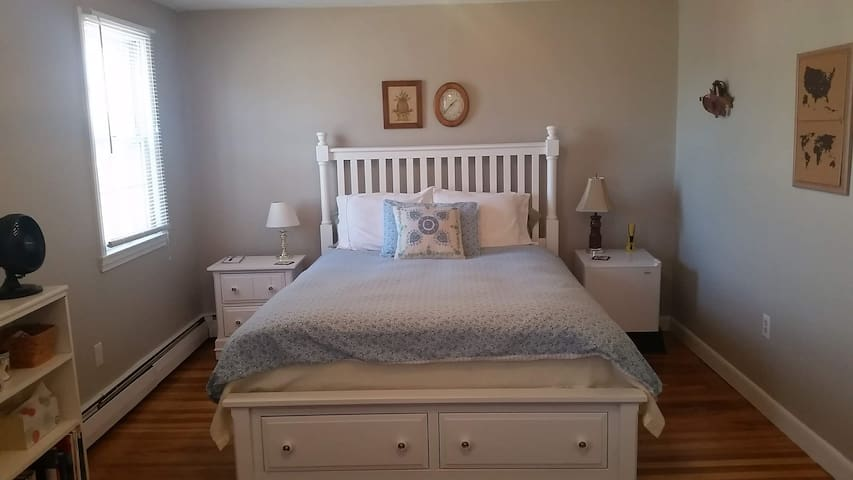 New queen sized bed.  Mini refrigerator, on the right, also serves as night stand.