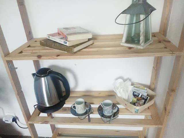 Bouilloire, tasses, sachets instantanés (café, chocolat, lait en poudre, thé, soupes), biscuits sucrés et salés, sucre ... à disposition dans la chambre.