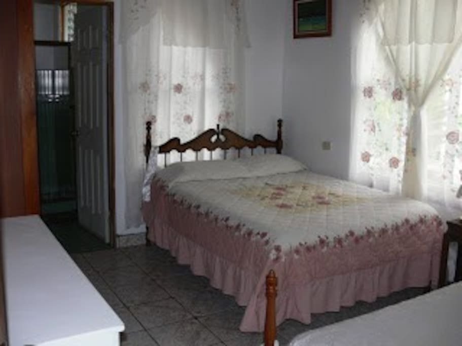 Private room II with one queen sized bed and one twin bed and bathroom.