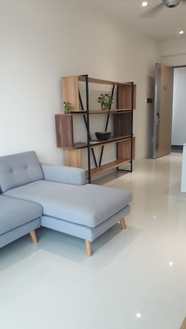Entrance door from couloir to living room: decorated wooden stand, sofa