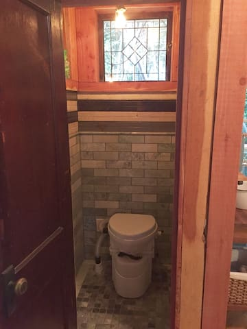 Composting water closet with stained glass and beautiful green marble subway tile.