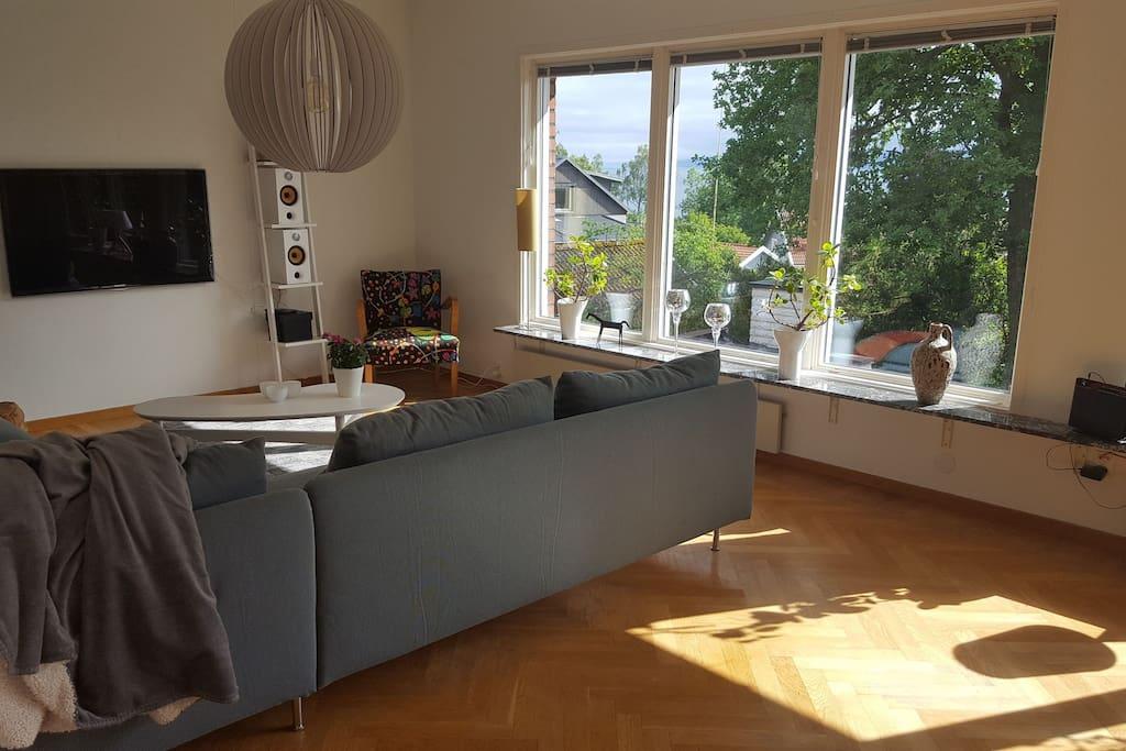 Vardagsrummet med stor hörnsoffa, 3×3 sits, fåtölj, TV.