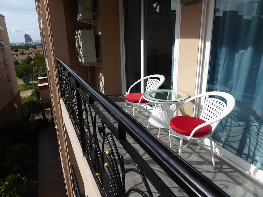 Stylish outdoor table and chairs with cushions on large balcony overlooking pool view