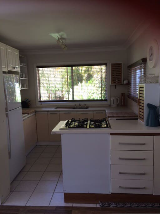 Open plan kitchen towards living and with view to yard with trampoline on far side