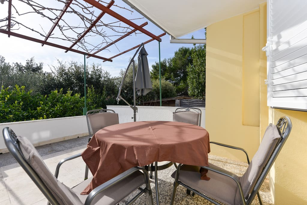 Terrace with dining table and sunshade