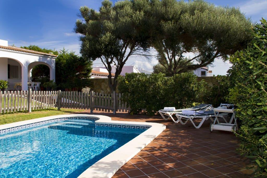 Jardín y piscina privada con mobiliario exterior