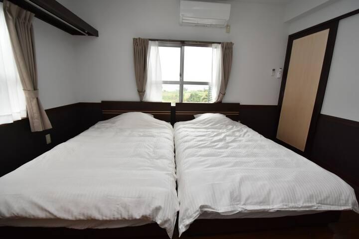 ベットルーム1。セミダブルベット2台。窓から気持ちの良い風が。冷房完備。隣の寝室とは開閉可能なドアで仕切られています。