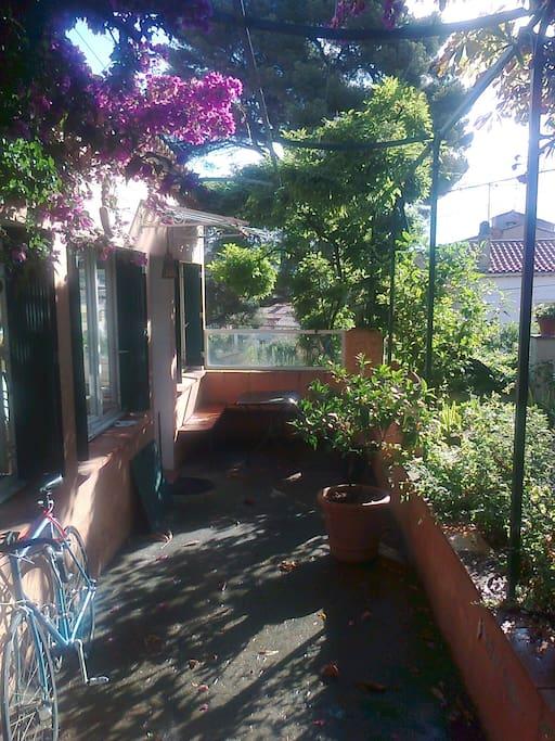 Coin repas sous la glycine entre le jardin et l'appartement.