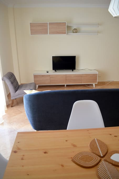 Spacious living room with TV and a table for 4