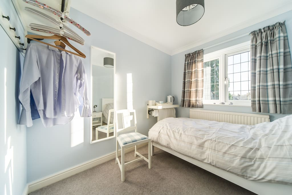 Rosemary bedroom showing hanging facilities and light bright decor.