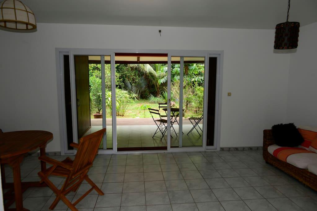 Salon/Salle à manger, vue sur la terrasse et le jardin.