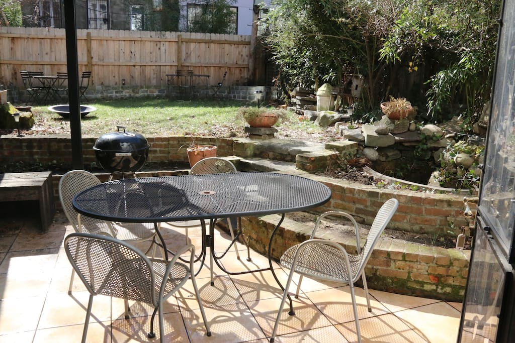 Garden terrace with table and grill.