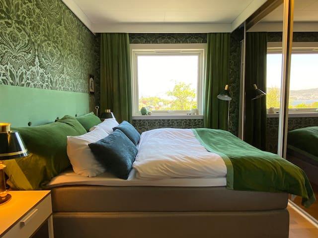 Deilig grønt soverom med stor speilgarderobe.