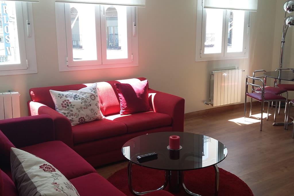 """salón muy luminoso con 3 ventanales a calle preciados. 2 sofás, mesa con 6 sillas, smart tv 48"""""""