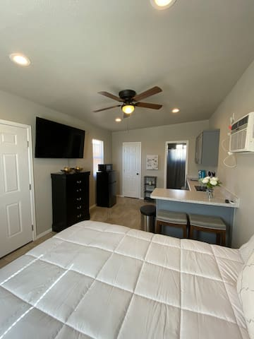 Cozy studio with a large TV, refrigerator, microwave, cooktop and kitchenette.