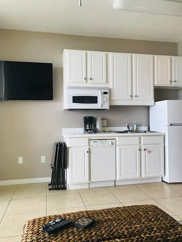 Kitchenette with a 2 burner cooktop, a convection microwave oven, a dishwasher, refrigerator, coffee maker, toaster and blender.