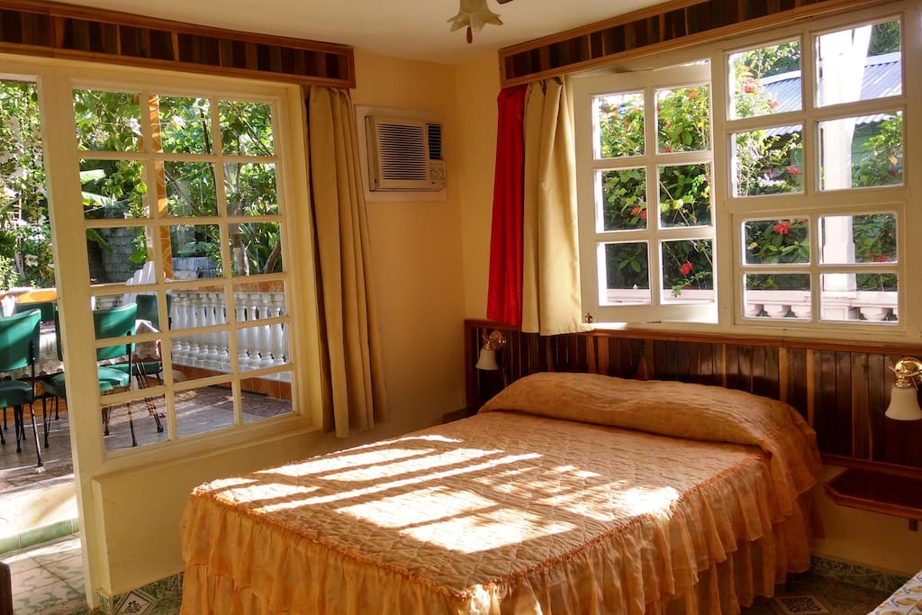 Room with large glass windows and excellent natural lighting looking over the delightful garden and terrace.