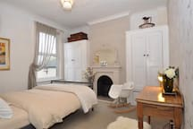 Victorian Room, queen size bed with lots of storage and a comfy wing back chair and desk and stool