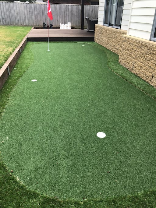 Synthetic 4 hole golf green with putters and balls
