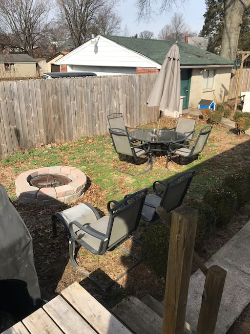Fenced backyard with fire pit and grill