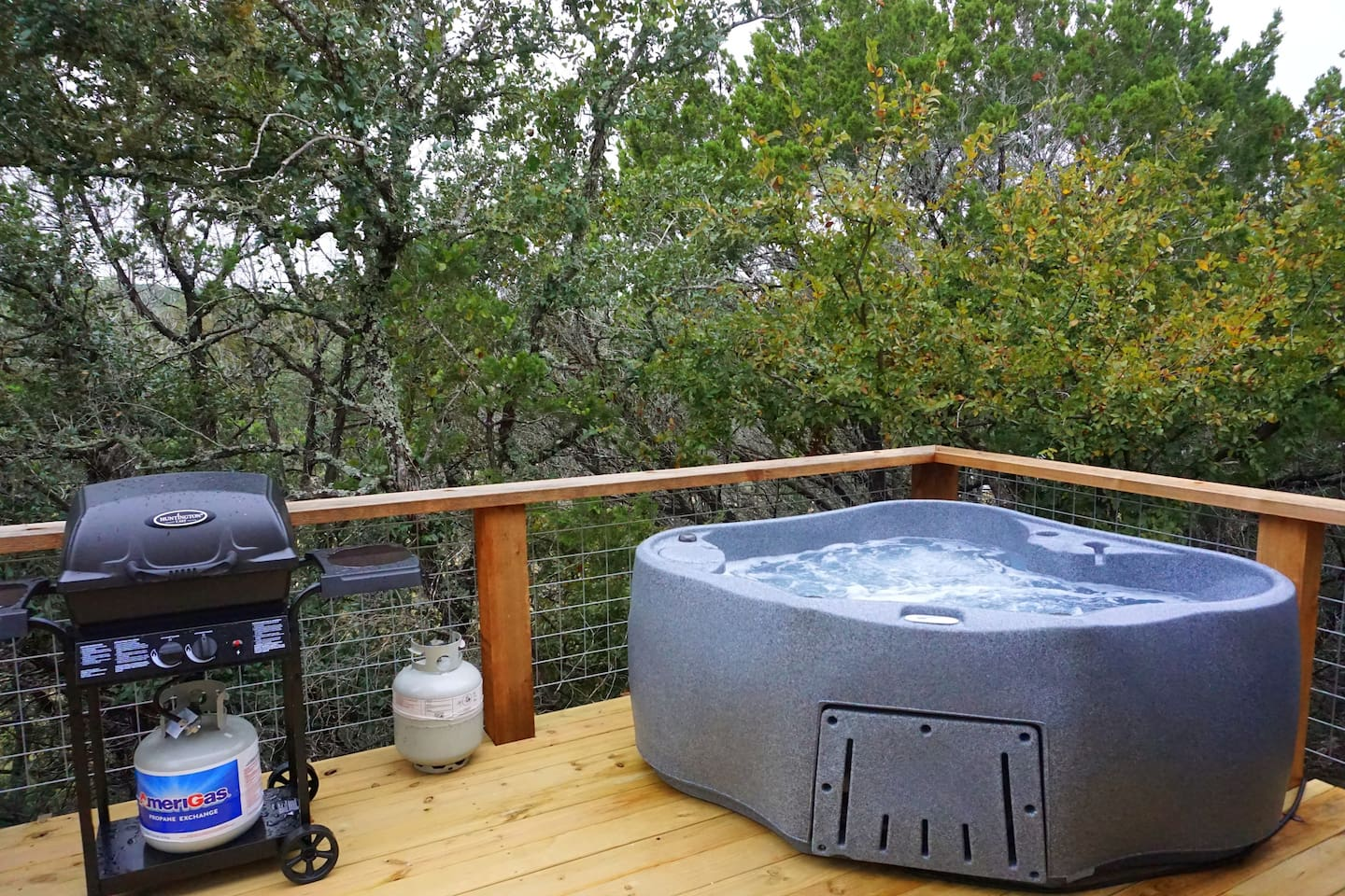 Hot tub and grill located on the back of the cabin
