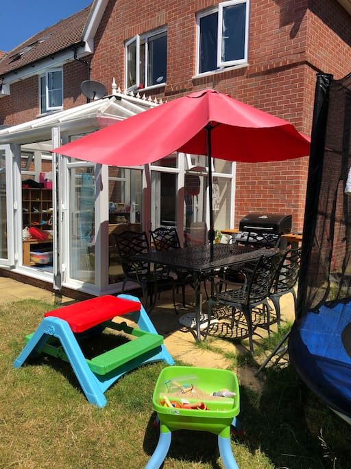 Back of house: Garden with gas BBQ, table & chairs for adults, picnic table for kids, swing, trampoline, dolls house & sand table