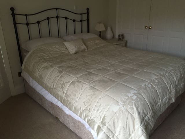 The second bedroom with ample wardrobe space , a desk and a king size bed