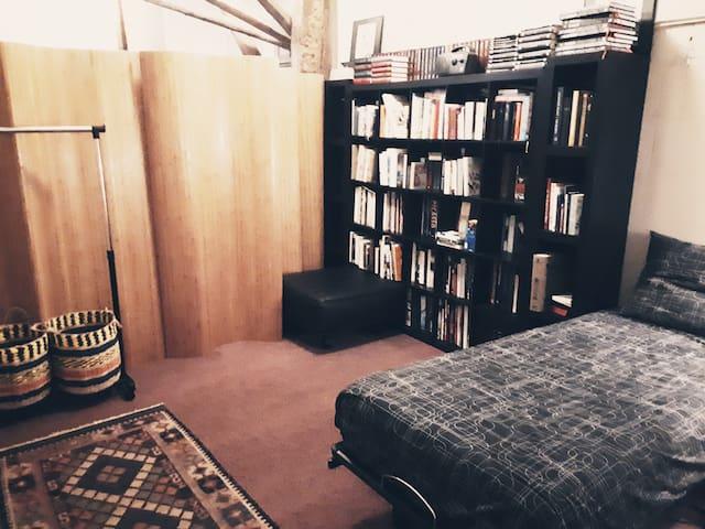 Tussenverdieping met in deze boekenkamer een twee persoonsbed.
