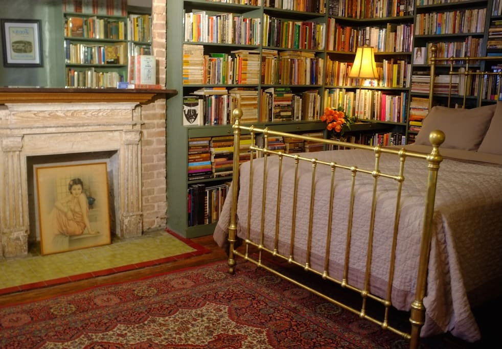Nineteenth Century brass queen sized bed, spaciously sleeps two, in the Private Library and all natural bed linens.