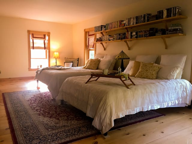 Main guest room has two queen size beds that are accompanied by comfy chairs.