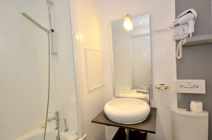 Salle de bain privative avec toilette, serviettes, sèche-cheveux, savon, gel douche, baignoire.