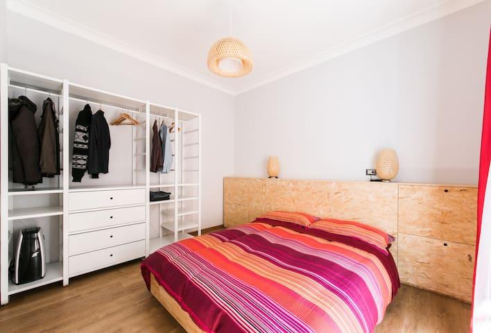 A cozy bedroom with a handy open wardrobe