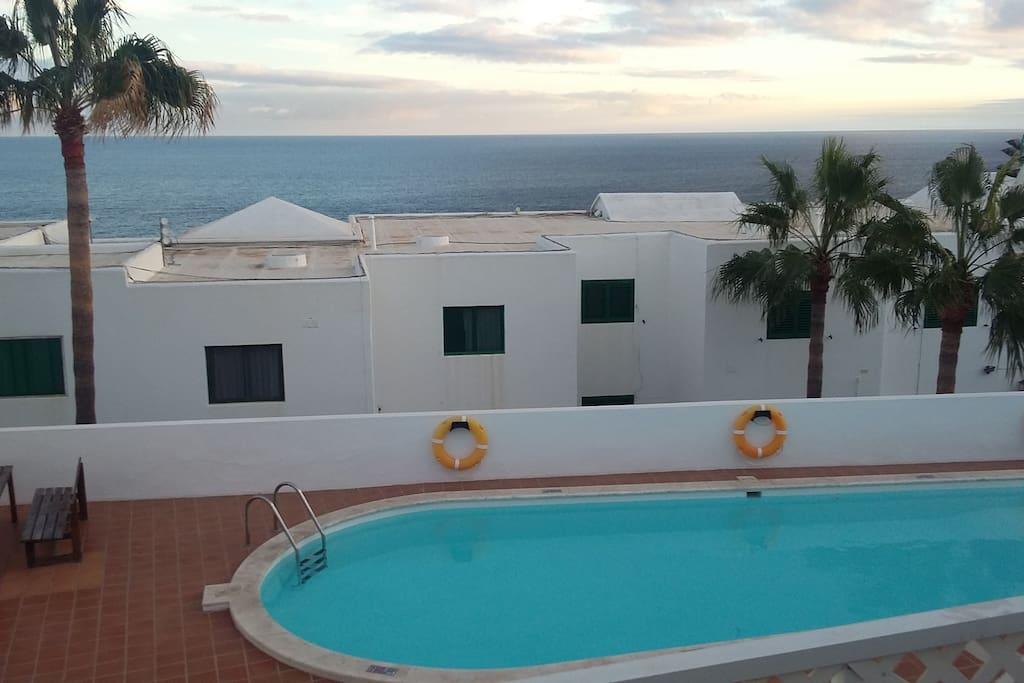 vista desde la terraza a la piscina comunitaria y al mar