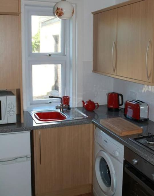Fully equipped kitchen area with washing machine