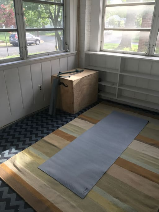 A front sun porch with yoga mats and equipment for stretching in the sun!