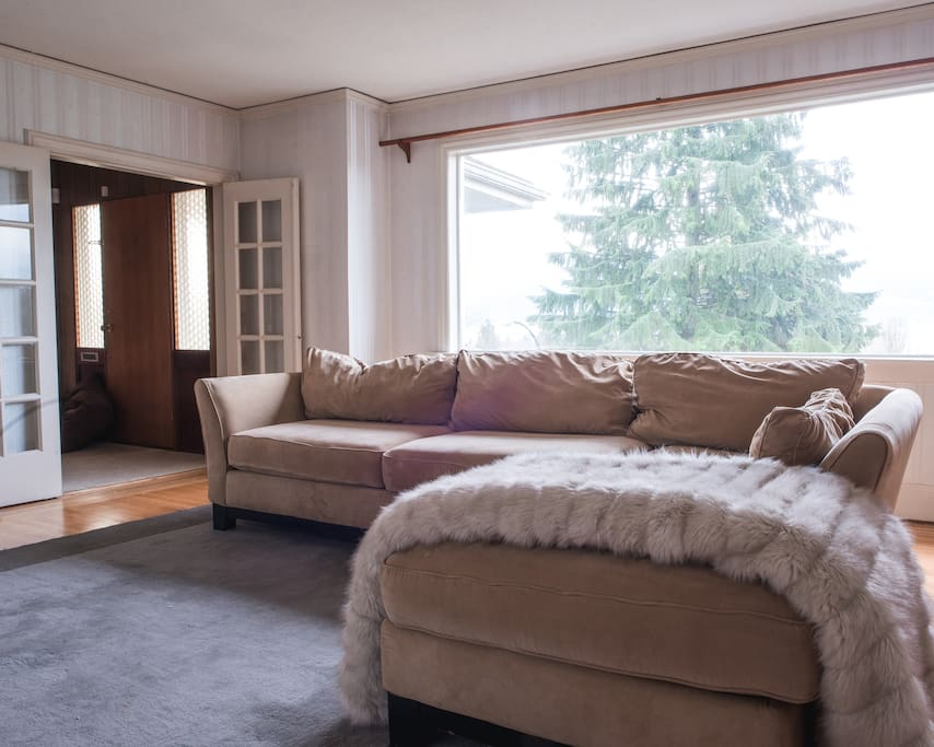 The couch lays on a soft comfortable rug with spectacular views behind it. With just a turn of the head, you can comfortably lounge on the sectional sofa with an amazing sign through the expansive window. This is truly an amazing spot to watch television.